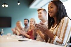 Groep Jonge Kandidaten die bij Bestuurskamerlijst het Toejuichen Presentatie bij Dag van de Bedrijfs de Gediplomeerde Rekrutering stock afbeelding