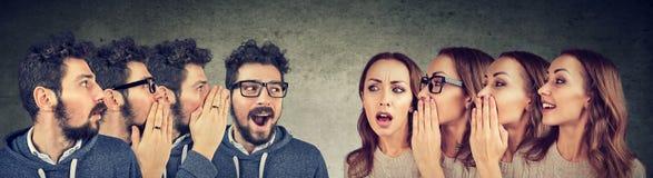 Groep jonge mannen en vrouwen die elkaar in het oor fluisteren stock afbeelding
