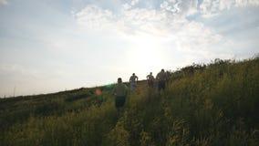 Groep jonge mensen die de groene heuvel over blauwe hemel met zongloed lanceren bij achtergrond De mannelijke atleten stoot binne Stock Afbeelding