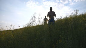 Groep jonge mensen die de groene heuvel over blauwe hemel met zongloed reduceren bij achtergrond De mannelijke atleten stoot binn Stock Fotografie
