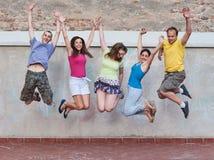Groep jonge mensen het springen Stock Foto's