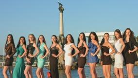 Groep jonge modellen in kleding en hoge die hielen tegen de achtergrond van het monument wordt gefotografeerd stock video