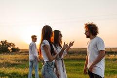 Groep jonge modieuze kerels die op de weg op een zonnige dag spreken royalty-vrije stock afbeelding