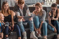 Groep jonge mooie multi-etnische vrouw en man vrienden die tegen een muur openlucht in de stad leunen die slimme telefoon met beh Stock Afbeeldingen