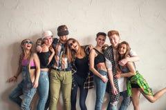 Groep jonge mooie vrouw en man vrienden die tegen een muur leunen binnen hebbend pret, vriendschapsconcept Stock Afbeeldingen
