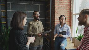 Groep jonge multi-etnische studenten die startproject disscussing terwijl zich het verenigen dichtbij venster in modern bureau stock video