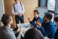 Groep jonge multiraciale bedrijfsberoeps die een vergadering in bestuurskamer hebben royalty-vrije stock afbeelding