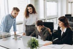 Groep jonge partners die in modern bureau werken Medewerkers die probleem hebben terwijl het werken aan laptop royalty-vrije stock foto