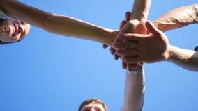 Groep jonge plaats hun handen samen in het centrum van een cirkel stock footage