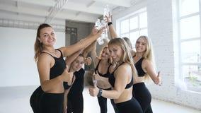 Groep jonge sportieve vrouwen die het eind van de flessen vieren die van een het trainen holdingswater teken o.k. na aerobics ton stock video