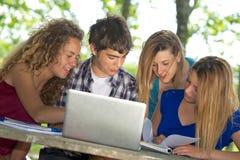 Groep jonge student die openlucht laptop met behulp van stock foto's