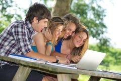 Groep jonge student die openlucht laptop met behulp van royalty-vrije stock foto