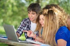 Groep jonge student die openlucht laptop met behulp van stock afbeelding