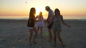 Groep jonge tieners die op een strand bij zonsopgang dansen stock videobeelden