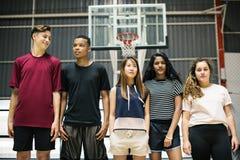 Groep jonge tienervrienden op een basketbalhof die zich op een rij bevinden stock afbeelding