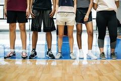 Groep jonge tienervrienden op een basketbalhof die zich op een rij bevinden stock fotografie