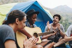 Groep jonge volwassen vrienden in kampeerterrein het spelen gitaar stock afbeeldingen