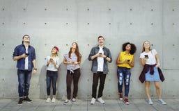 Groep jonge volwassenen die in openlucht smartphones omhoog het kijken gebruiken royalty-vrije stock foto