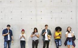 Groep jonge volwassenen in openlucht smartphones samen en CH die gebruiken stock afbeelding