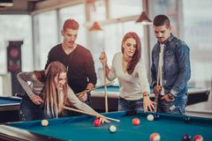 Groep jonge vrienden die biljart spelen royalty-vrije stock afbeelding