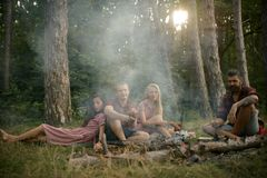 Groep jonge vrienden die in bos Twee paren kamperen die van picknick op warme de zomeravond genieten Het vermoeide gebaarde mens  royalty-vrije stock foto's