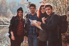 Groep jonge vrienden die in de herfst kleurrijk bos wandelen, bekijkend kaart en planningsstijging stock afbeeldingen
