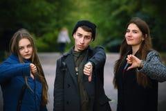 Groep jonge vrienden die duim neer tonen stock afbeeldingen