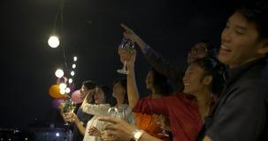 Groep jonge vrienden die en pret het vieren Nieuwjaar en Kerstmisfestival hebben samen bij de zomerdak dansen