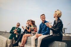 Groep jonge vrienden die op terras partying stock foto