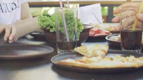 Groep jonge vrienden die pizza in openlucht eten stock footage