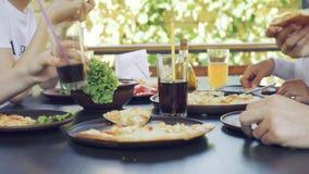 Groep jonge vrienden die pizza in openlucht eten stock videobeelden