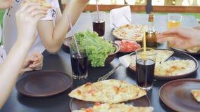 Groep jonge vrienden die pizza in openlucht eten stock video