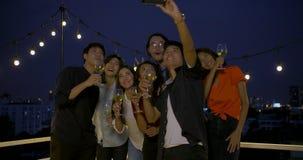 Groep jonge vrienden die pret het vieren Nieuwjaar en Kerstmisfestival hebben samen bij de zomerdak