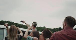 Groep jonge vrienden die selfies bij de aard nemen, zij die en, naast tribune zich keurig springen bewegen een retro bestelwagen stock footage