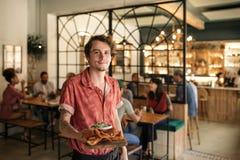 Groep jonge vrienden die tot voedsel in een restaurant opdracht geven Royalty-vrije Stock Fotografie