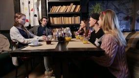 Groep jonge vrienden die uit bij koffiewinkel hangen stock videobeelden
