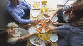 Groep jonge vrienden die van een diner genieten die tijdens het eten van pizza spreken royalty-vrije stock foto