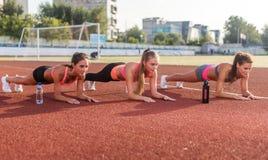 Groep jonge vrouwen die plank samen in stadion doen stock foto