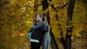 Groep Jonge vrouwen die vóór yogaoefeningen samenkomen in het park van de de herfststad Het concept van de gezondheidslevensstijl stock footage