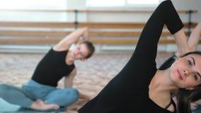 Groep jonge vrouwen die yoga het uitrekken in de geschiktheidsklasse maken zich stock video