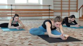 Groep jonge vrouwen die yoga het uitrekken in de geschiktheidsklasse maken zich stock videobeelden