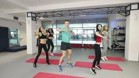 Groep jonge vrouwen in geschiktheidsklasse die oefeningen voor de benen met trainer maken stock footage