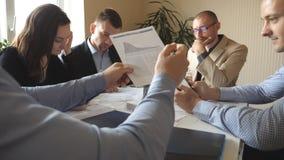 Groep jonge zakenlieden die bij lijst in modern bureau zitten en aan nieuw project werken De collega's herzien zorgvuldig stock videobeelden