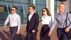 Groep jonge zakenlieden die bij stadsstraat tijdens zonnige dag lopen Collega's die op zijn manier aan zakenreis zijn stock videobeelden