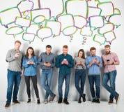 Groep jongens en meisjes aan hun smartphones worden verbonden die Concept Internet en sociaal netwerk stock afbeelding