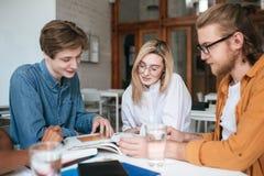 Groep jongeren die bij de lijst zitten en in bureau samenwerken Mooi meisje en twee jongens die gelukkig bespreken royalty-vrije stock foto's
