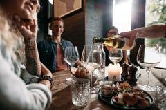 Groep jongeren die dranken hebben bij restaurant royalty-vrije stock afbeelding
