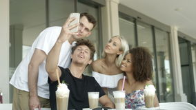 Groep jongeren die in een restaurant en nemen selfies zitten stock footage