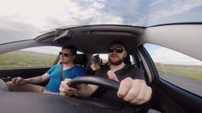 Groep jongeren die naar de reis door auto samen gaan Gelukkige vrienden die op gopro filmen en aan muziek dansen stock video