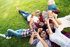 Groep jongeren die op het gras in cirkel, duimen leggen upGroup van jongeren die op het gras in cirkel leggen, die telefoons met  stock foto